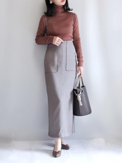 ブラウンのリブニット×グレーのサロペットスカート×ブラウンのパンプス×ブラウンのバッグ