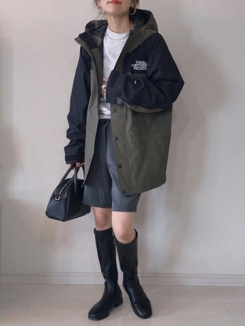 ロングブーツ×マウンテンパーカー×白のTシャツ×グレーのショートパンツ×黒のバッグ