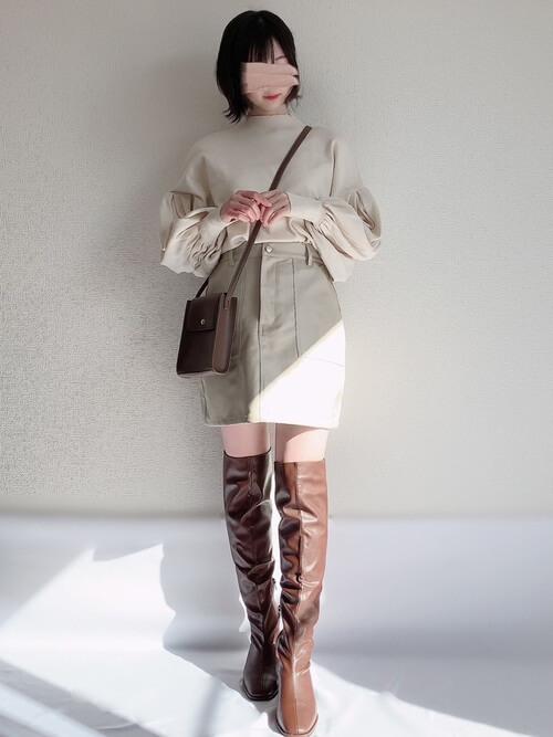 ロングブーツ×ベージュのニットセーター×ベージュのミニスカート×ブラウンのバッグ
