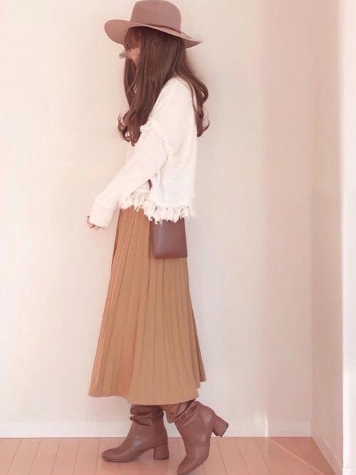 キャメルのロングブーツ×白のニット×ブラウンのプリーツスカート×ブラウンのハット