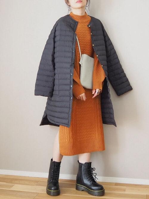 編み上げブーツ×黒のダウンコート×オレンジのニットワンピース×ベージュのバッグ