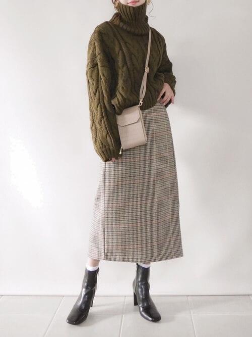 タイトスカート×グリーンのタートルネックニット×黒のブーツ×ベージュのバッグ