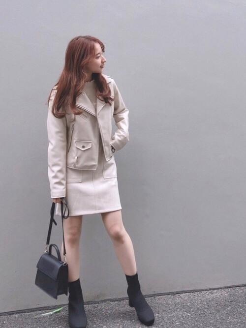 白のライダースジャケット×白のニット×白のミニスカート×黒のブーツ×黒のバッグ