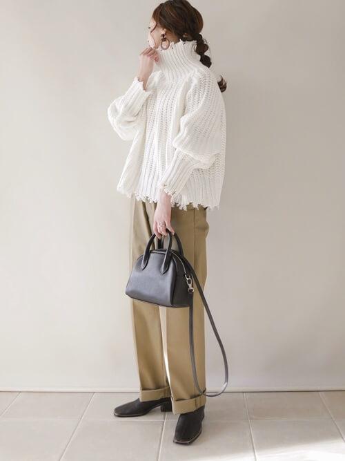 ベージュのチノパンツ×白のダメージニット×黒のブーツ×黒のバッグ