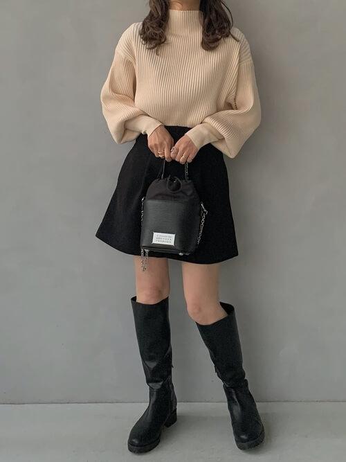 ロングブーツ×ベージュのハイネックニット×黒のミニスカート×黒のバッグ