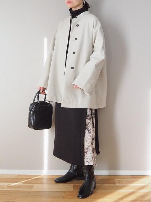 ロングブーツ×ベージュのコート×黒のワンピース×黒のバッグ