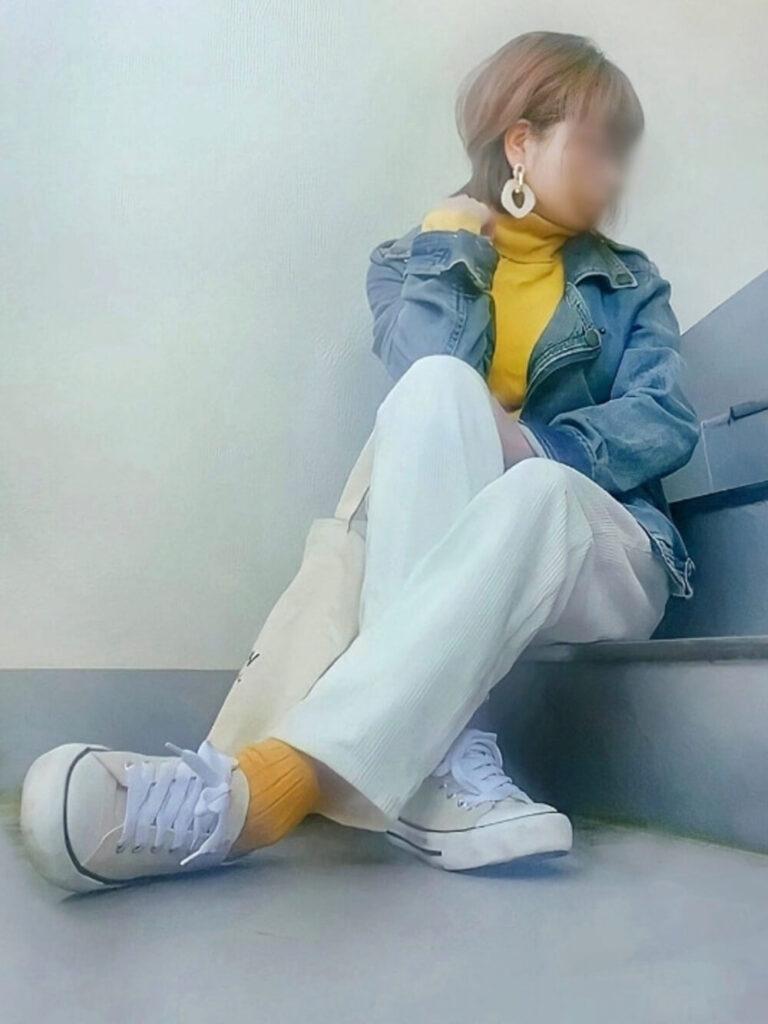 黄色のタートルネック×白のコーデュロイパンツ×カラーソックス×スニーカー×青のライダースジャケットの秋冬コーデ