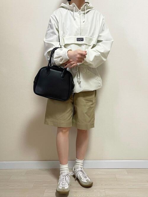 アノラックパーカー×ベージュのショートパンツ×白のスニーカー×黒のバッグ