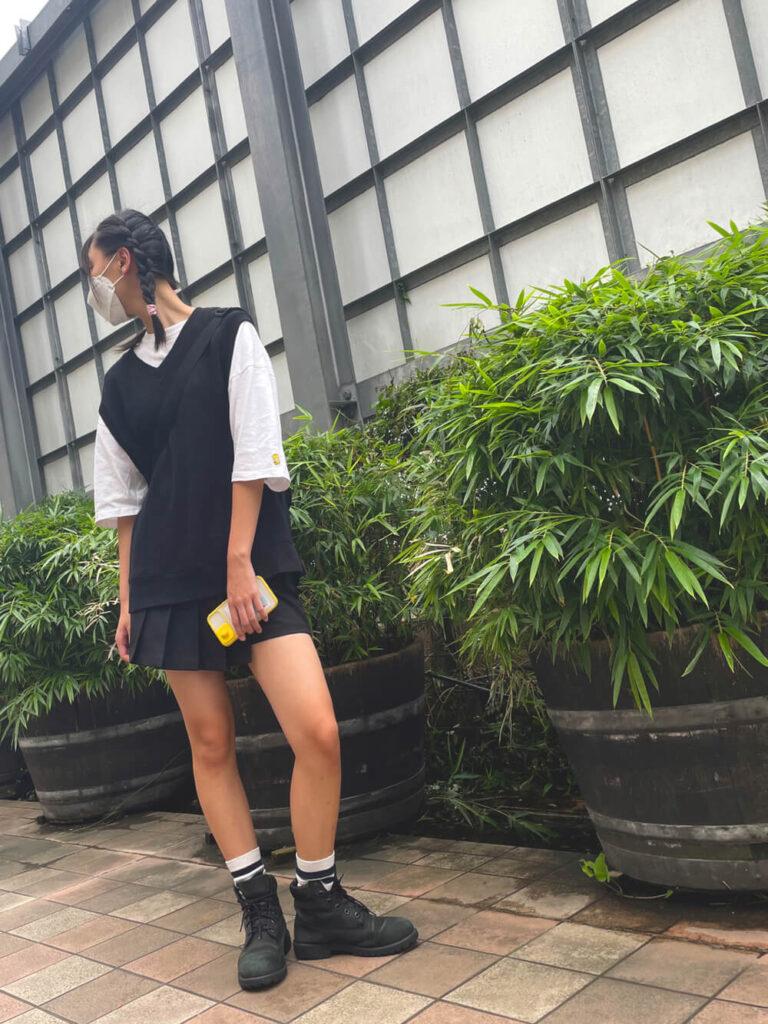 白のオーバーTシャツ×黒のベスト×ミニプリーツスカート×ティンバーランドブーツのレディースコーデ