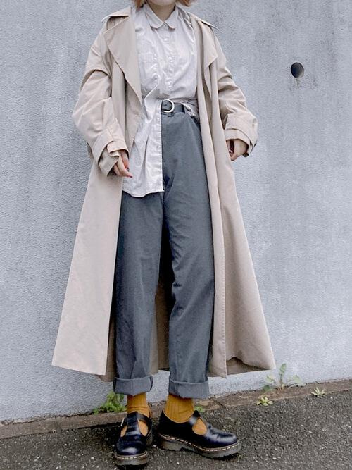 ベージュのトレンチコート×ベージュのシャツ×グレーのパンツ×オレンジのソックス×黒のブーツ