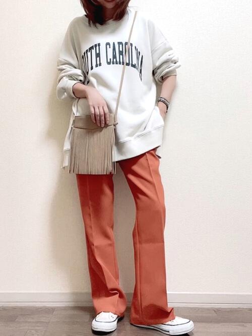 白のトレーナー×オレンジパンツ×白のスニーカー×ベージのフリンジバッグ