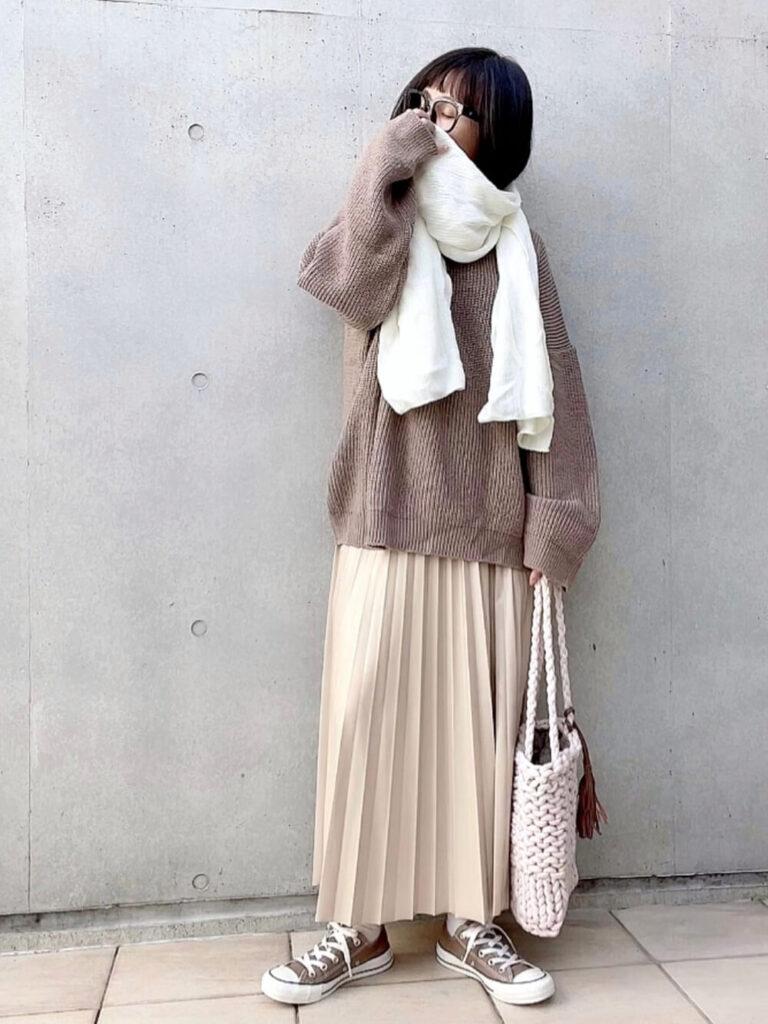 茶色のニット×プリーツスカート×スニーカー×白のマフラー・ストールのコーデ