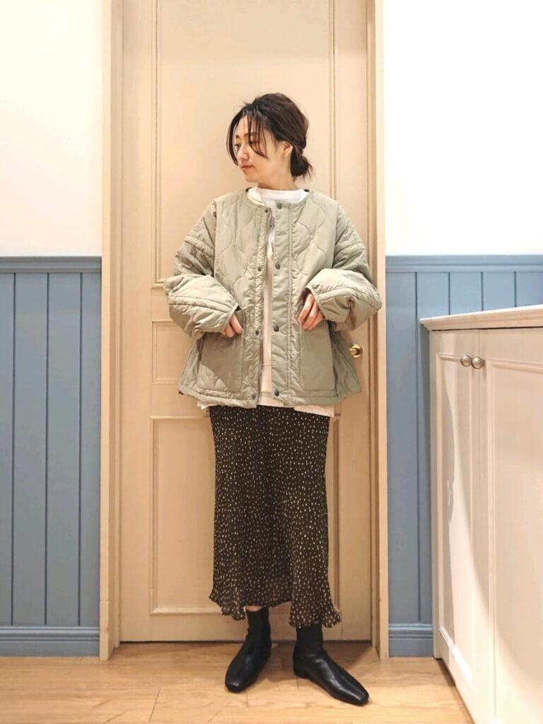 白のカットソー×ドット柄スカート×ショートブーツ×緑ダウンのレディースコーデ