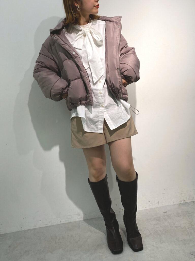 白のブラウス×ベージュのショートパンツ×ロングブーツ×ショート丈のダウンジャケットのレディースコーデ
