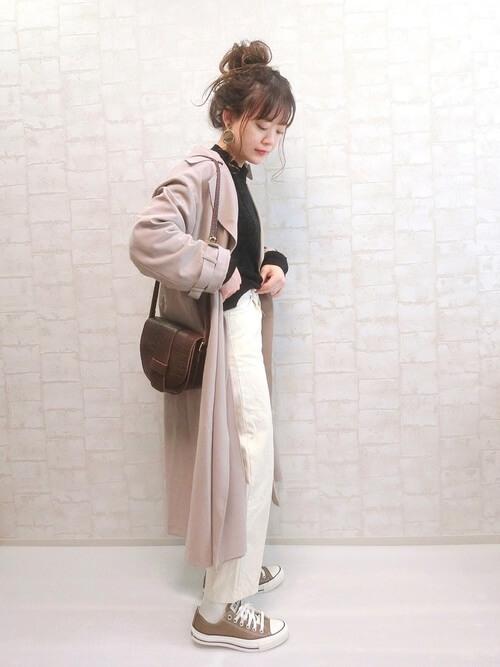 ピンクのトレンチコート×黒のニット×白のパンツ×ベージュのスニーカー×ブラウンのバッグ