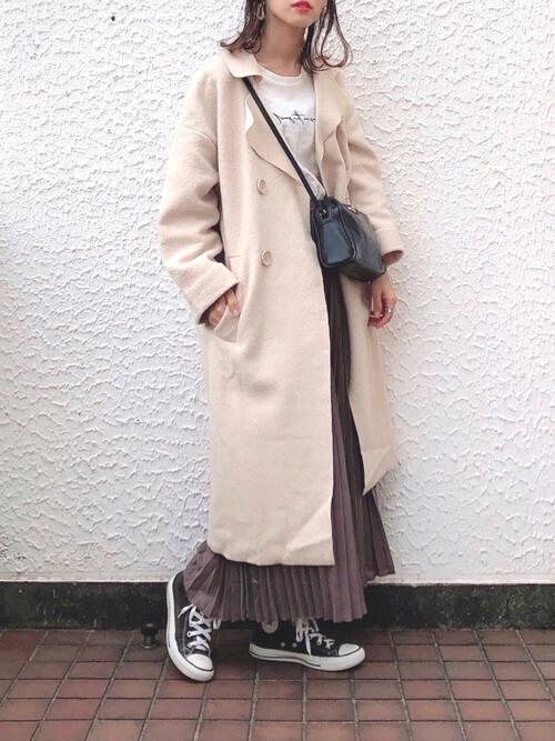 ベージュのチェスターコート×白のロゴTシャツ×ブラウンのプリーツスカート×黒のスニーカー