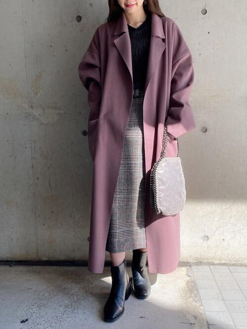 ピンクのトレンチコート×黒のニット×グレンチェック柄のスカート×黒のブーツ