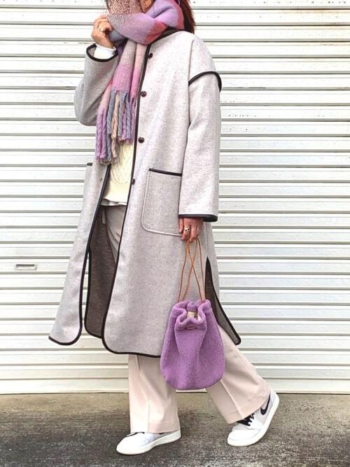 ピンクのマフラー×ベージュのノーカラーコート×ベージュのパンツ×白のスニーカー×パープルのバッグ