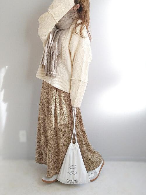 ベージュのマフラー×白のケーブルニット×総柄のベージュのスカート×白のスニーカー