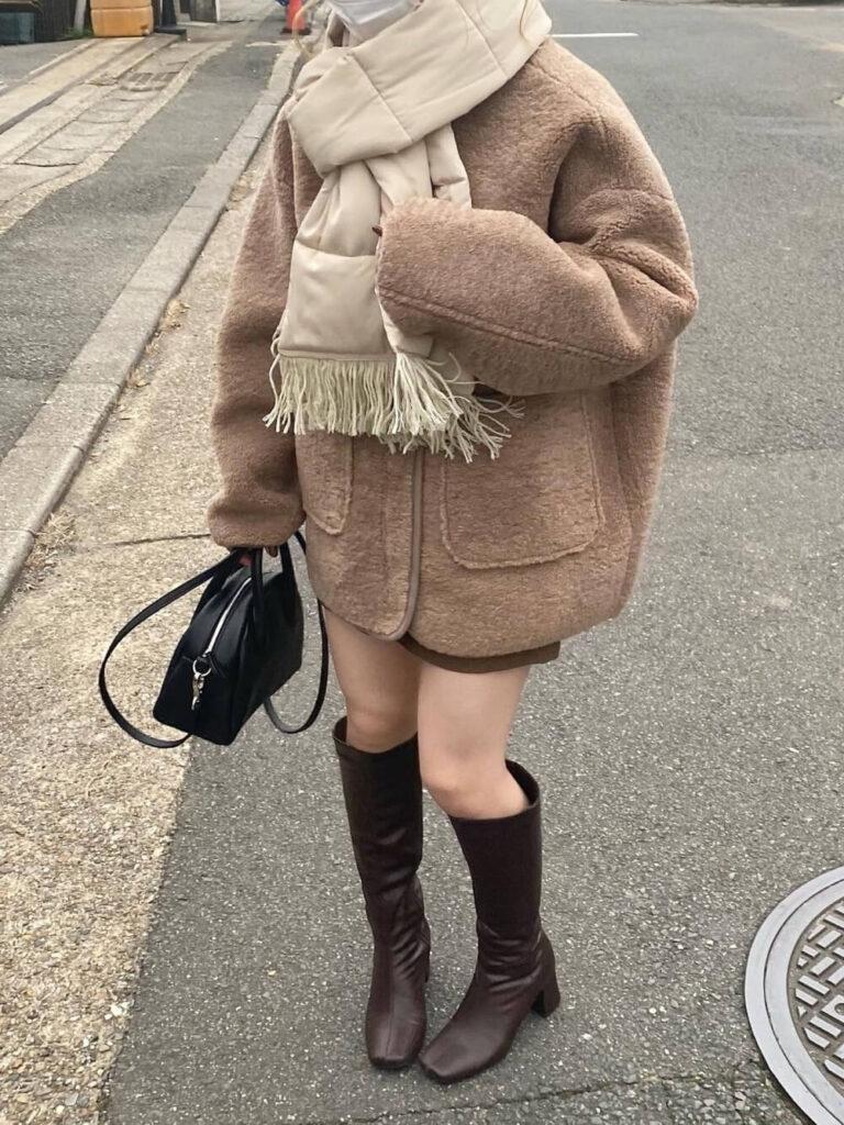 茶色のジャケット×茶色のショートパンツ×ロングブーツ×白のマフラー・ストールのコーデ