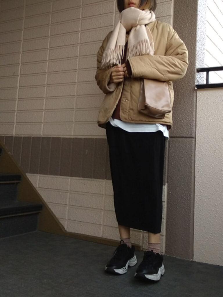 キルティングジャケット×黒のタイトスカート×スニーカー×白のマフラー・ストールのコーデ