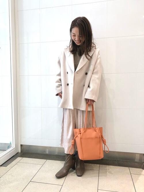 Pコート×ブラウンのニット×白のスカート×ブラウンのブーツ×オレンジのバッグ