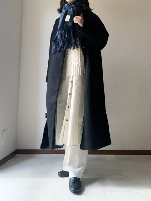 ネイビーのマフラー・ストール×黒のノーカラーコート×白のニットベスト×白のシャツワンピース×白のパンツ×黒の靴