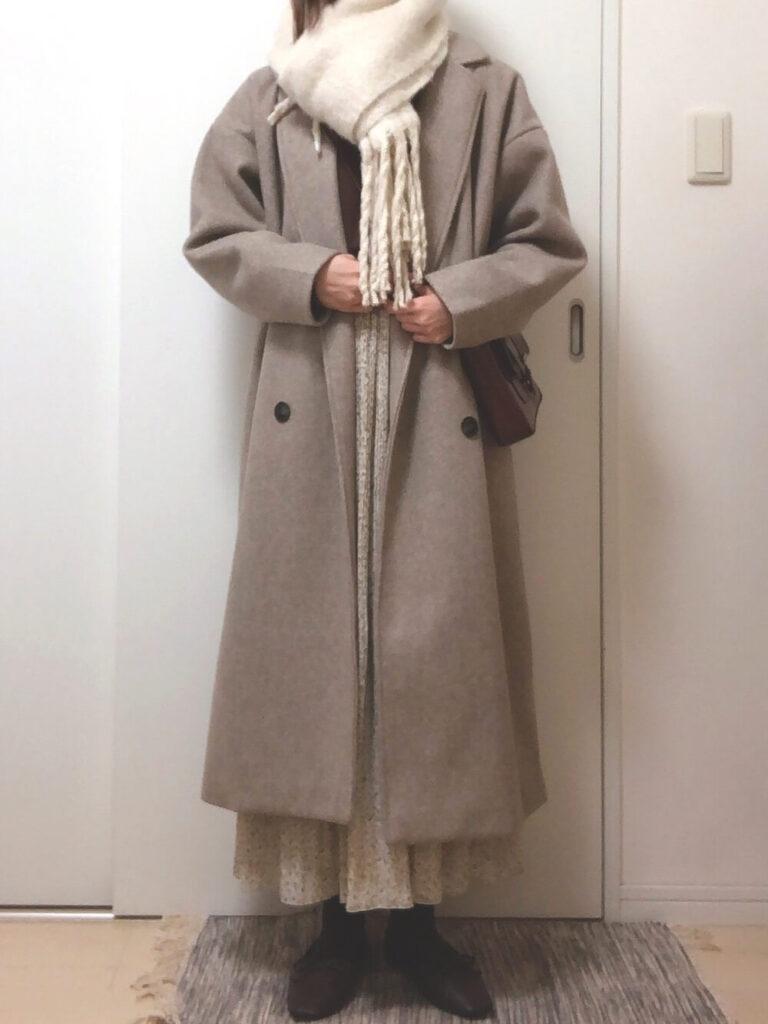 ベージュのチェスターコート×茶色のスウェット×プリーツスカート×白のマフラー・ストールのコーデ