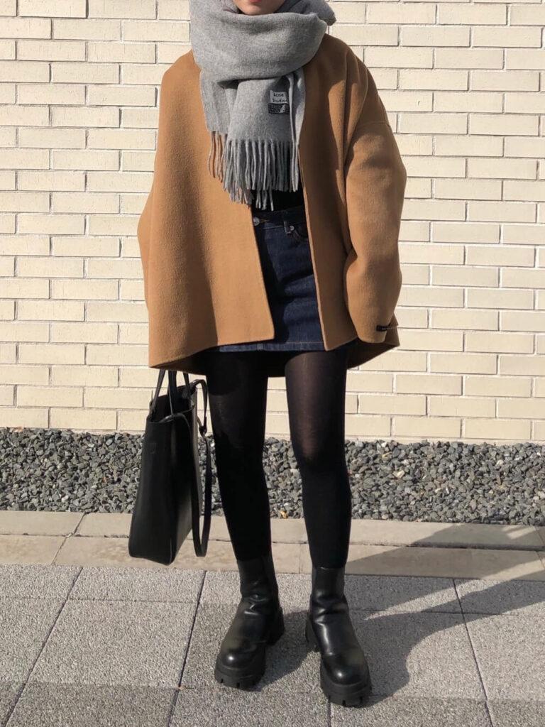 黒のカットソー×茶色のジャケット×デニムミニスカート×ショートブーツ×グレーのマフラー・ストールのレディースコーデ