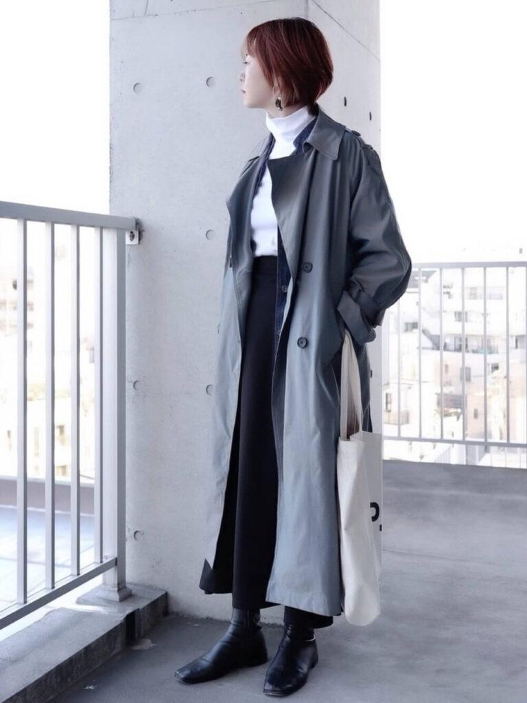 白のタートルネック×黒のフレアスカート×ショートブーツ×ネイビーのトレンチコートの秋冬コーデ