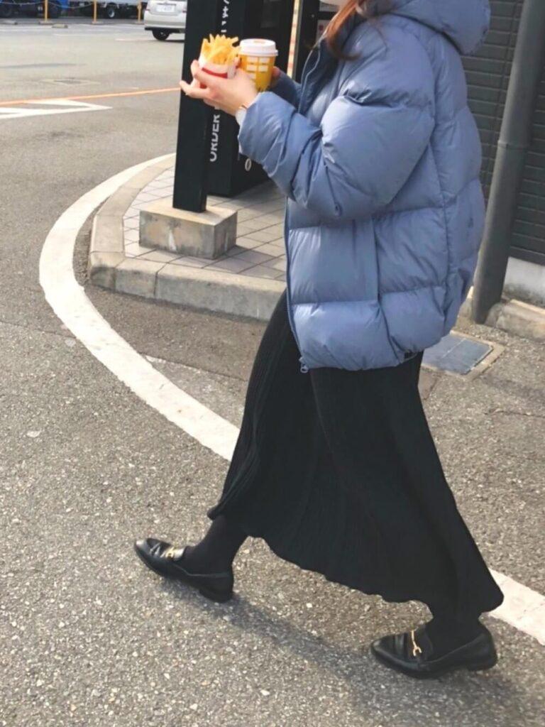 黒のプリーツスカート×黒タイツ×ビットローファー×ビックシルエットのダウンジャケットのレディースコーデ