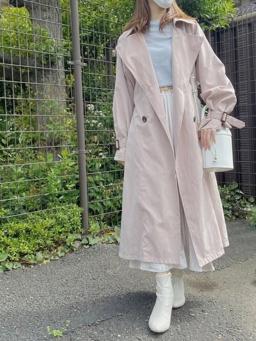 ピンクのトレンチコート×青系ニット×白のスカート×白のブーツ