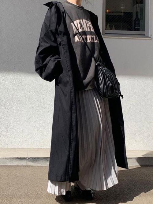 黒のトレンチコート×黒のロゴトレーナー×ベージュのプリーツスカート×黒のパンプス