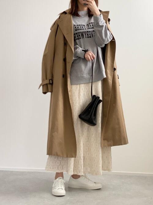 レーススカート×スニーカー×ブラウンのトレンチコート×グレーのスエット×黒の巾着バッグ